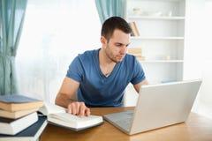 他的使用的工作笔记本学员 免版税库存图片