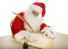 他的做圣诞老人的列表 免版税库存照片