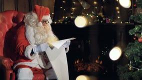 他的圣诞老人在圣诞树附近的椅子读新年礼品单的 影视素材