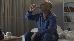 他的坐在床上和采取抗抑郁剂的50s的被用尽的人在晚上 免版税库存照片