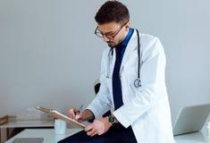 他的患者的确信的男性医生文字信息在办公室 库存图片