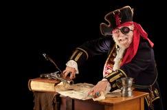 他的指向珍宝的映射海盗 免版税库存照片