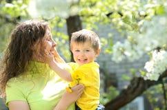 他的母亲的胳膊的微笑的小男孩 免版税库存照片