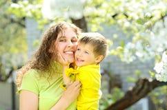 他的母亲的胳膊的微笑的小男孩 免版税图库摄影