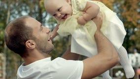 他的父亲阻止的愉快的微笑的婴孩在秋天公园 免版税图库摄影