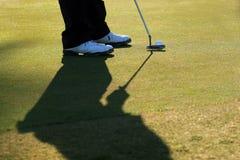 他的线路轻轻一击的高尔夫球运动员 免版税库存照片