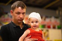 他的胳膊的疲乏的爸爸藏品女儿,父权概念 免版税库存图片
