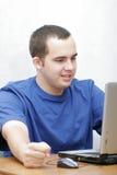 他的膝上型计算机学员工作 免版税库存图片