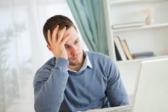 他的膝上型计算机的疲乏的人 免版税库存照片