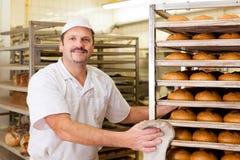 他的面包店烘烤面包的贝克 免版税库存图片