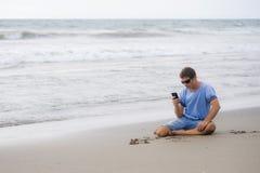 他的30s的可爱和英俊的人坐沙子在海滩放松了笑在海前面的发短信在流动pho 库存照片