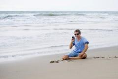 他的30s的可爱和英俊的人坐沙子在海滩放松了笑在海前面的发短信在流动pho 免版税库存照片