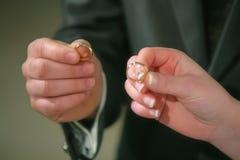 他递新娘和新郎与圆环在手上在教会里 图库摄影