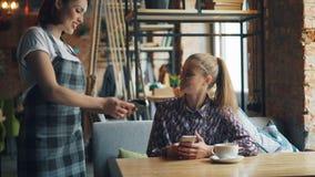 付与智能手机的女性顾客网上付款支付在咖啡馆的食物 影视素材