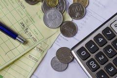 付款与印度尼西亚卢比和新加坡元硬币的收据演算、计算器和发货票在顶视图/平的位置 免版税库存图片