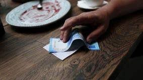 付现金的人在咖啡馆的票据 纸币钞票在人有餐馆的` s手上检查木桌 影视素材