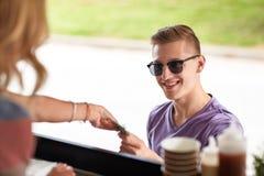 付钱的愉快的年轻人在食物卡车 免版税库存照片