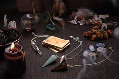 仙境辅助部件 老占卜卡片和一把石摆锤甲板  免版税库存图片