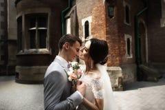 令人惊讶的微笑的婚姻的夫妇 俏丽的新娘和时髦的新郎在教会附近 免版税库存图片