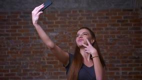 令人惊讶的白种人姜女性显示她的幸福,当拍在她的智能手机时网照相机的selfie照片  股票视频