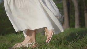 令人惊讶的白色礼服的未被认出的逗人喜爱的妇女走在公园的 t 影视素材
