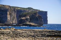 令人惊讶的真菌和Gebla岩石峭壁在Dwejra海湾海滩在倒塌的天蓝色的窗口,戈佐岛海岛,马耳他附近 库存图片