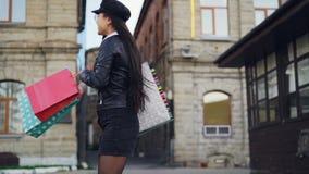 令人愉快的少妇亚裔学生慢动作画象获得与转动的购物袋的乐趣在街道和 股票录像