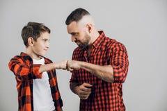 令人敬畏的年轻人和小男孩互相招呼 免版税库存照片