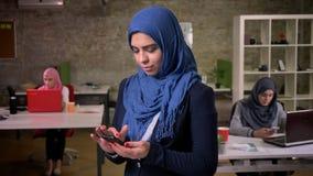 令人敬畏的抽烟的阿拉伯人女性在深蓝hijab在砖办公室使用她的智能手机,当站立在其他附近时 股票录像