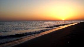令人满意镇静减慢碰撞在沙子海滩在印象深刻的温暖的晚上橙色日落海景的海岸海岸线的波浪 股票录像