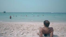 令人激动的夫人在太阳点燃的黄沙海滩晒日光浴 股票录像