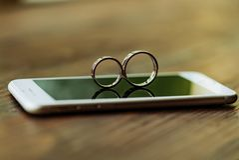 """以""""8""""字形的形式两个婚戒在电话在屋子里 他们在屏幕的背景被显示 免版税库存图片"""