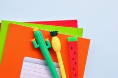 以一个仙人掌、西瓜、菠萝和色的笔记本的形式明亮的文具笔在蓝色背景 backarrow 库存图片