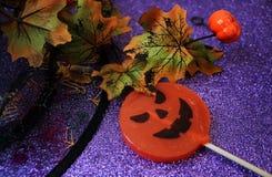 以一个南瓜的形式糖果为在精采背景的万圣夜与装饰的万圣夜 万圣节 免版税库存照片