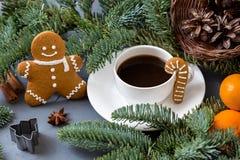 以一个小人的形式曲奇饼在圣诞节桌上 一杯咖啡,蜜桔,云杉的枝杈 图库摄影