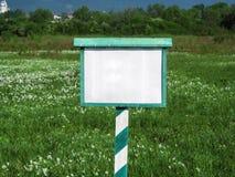 以一个开花的谷为背景的空白的白色和绿色标志特写镜头在夏天 免版税图库摄影