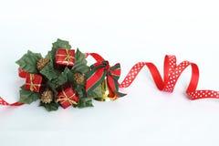 以一个杉树冠的形式圣诞节装饰在与一条红色丝带、金铃、绿色叶子和红色的白色背景 库存图片