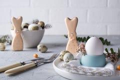 以一个滑稽的兔宝宝、鹌鹑蛋和鸡的形式自创复活节曲奇饼怂恿 复活节庆祝桌设置 库存图片