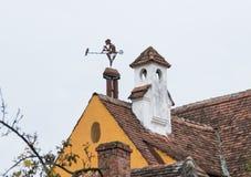 以一个男孩的形式风标有一个管子和一只鸟的在一个寓所的屋顶在老城Sighisoara在罗马尼亚 图库摄影
