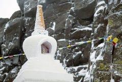 以一个被弄脏的积雪的岩石为背景的佛教stupa 库存照片