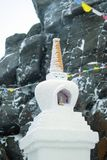 以一个被弄脏的积雪的岩石为背景的佛教stupa 免版税库存图片