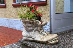 以一双鞋子的形式石罐有在房子的门阶的花的 免版税图库摄影