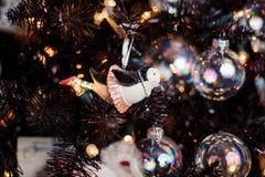以一只企鹅的形式逗人喜爱的圣诞树装饰玩具在裙子 免版税库存照片
