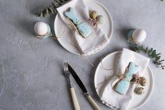 以一只滑稽的兔子的形式自创复活节曲奇饼在白色板材 复活节欢乐桌设置 免版税库存图片