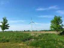 以一台风轮机为特色的国家边的风景在发电的一个明亮的夏日 免版税库存图片