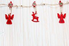 以一头鹿和一条天使绳索的形式圣诞节木红色玩具在白色木背景 美丽的欢乐贺卡 免版税库存照片