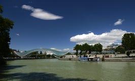 以一把匕首的形式一朵白色云彩以在步行桥和平上的一天空蔚蓝为背景在第比利斯 免版税库存照片