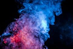 以一朵云彩的形式密集的呼气的蓝色紫色和白色烟在黑背景顺利地搬入溶化的蒸气 免版税库存图片