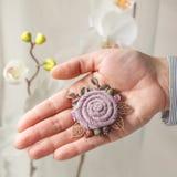 以一朵大淡紫色花的形式小手工制造别针从在您的手棕榈的织品  库存图片