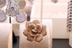 以一朵花的形式华美的昂贵的圆环与金刚石 库存照片